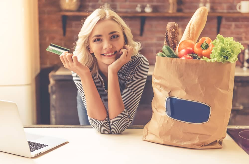 woman standing with her bag of groceries that she bought online
