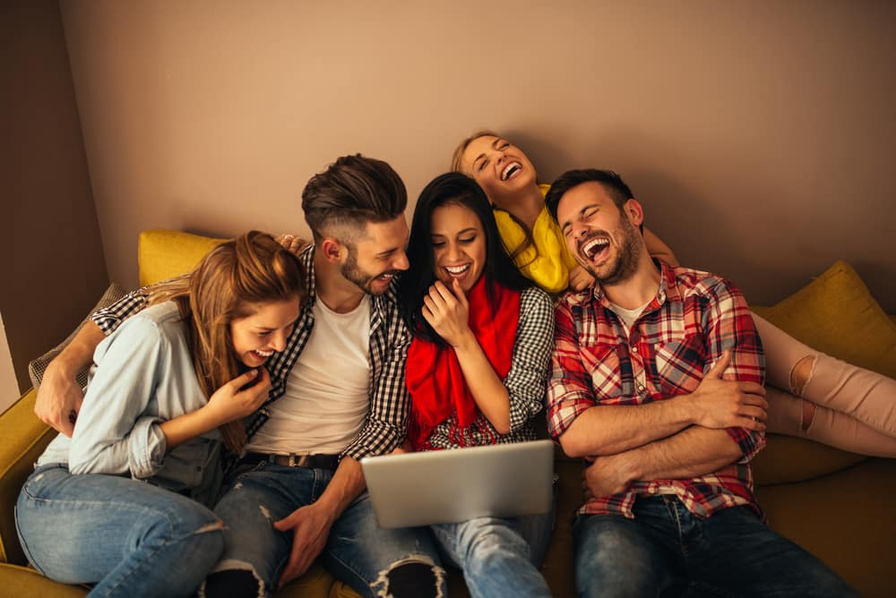 five friends sit together and laugh on a couch while watching a funny video on a laptop
